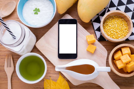 wood table with Blank screen on smart phone, tablet, cell phone  with breakfast.
