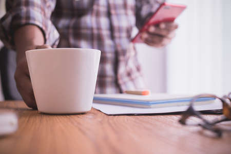 businessman using smartphone and drink coffee. selective focus on coffee cup.