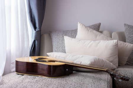 letto bianco con chitarra nel soggiorno. Archivio Fotografico
