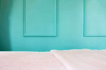 white bed on blue wall background in bedroom, copy space.