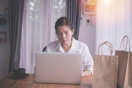 asian elderly woman using laptop for shopping online at home, front view.