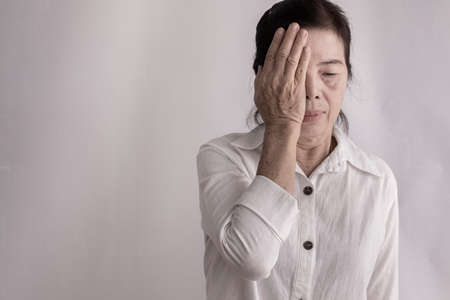 femme âgée asiatique ayant des douleurs oculaires sur fond isolé, concept de mode de vie sain.