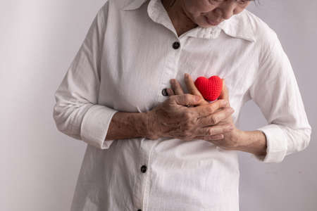 asian elderly woman hold red heart shape, concept of heart disease, front view.