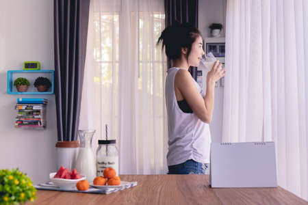 Standing woman drinking milk in living room at home, young asian woman lifestyle.