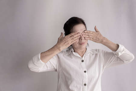 asian elderly woman Stinging eyes on isolated background, concept of health care.