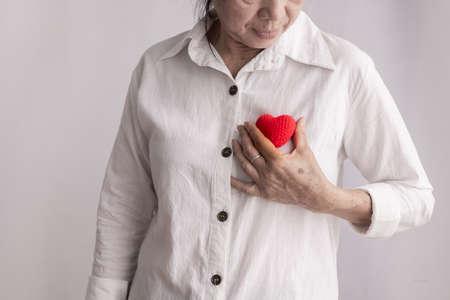 femme âgée asiatique souriante tenant une forme de coeur rouge, concept de prévention des maladies cardiaques, vue de face.