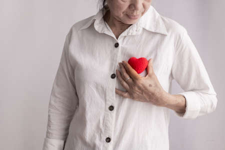 smiling asian elderly woman holding red heart shape, concept of prevention heart disease, front view. Zdjęcie Seryjne