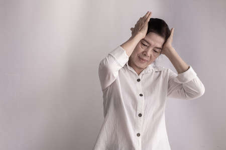 asian elderly woman having headache on isolated background, concept of health lifestyle.