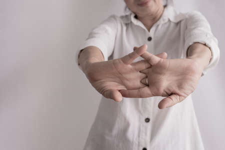 asian elderly woman stretching hand on isolated background, concept of healthy care.