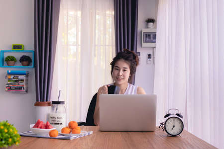 kitchen table with young asian woman drinking coffee, young asian lifestyle.