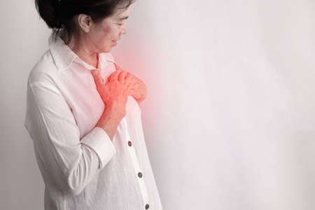 asian elderly woman having Chest pain on isolated white background, side view.