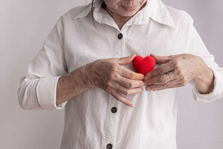 smiling asian elderly woman holding red heart shape, concept of prevention heart disease, front view. 免版税图像