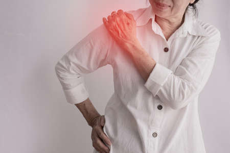 asian elderly woman having Shoulder pain on isolated white background, concept of healthy care.