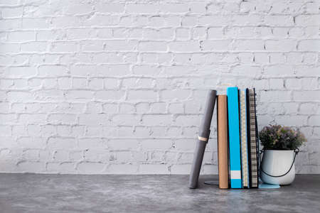 book and notebook paper on brick wall in home, front view table. Stock Photo