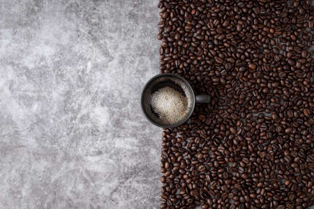 hot coffee cup with coffee beans, view from above table.