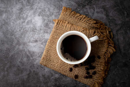 Black coffee mug and coffee beans on cement texture background. 版權商用圖片