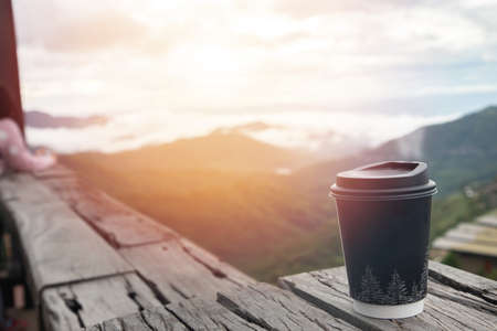 hot coffee cup on wood table with scenery view in morning. 版權商用圖片