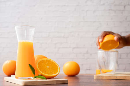 wood table with Jug of Freshly Squeezed Orange juice with human hand Squeezing orange, No Added Sugar.