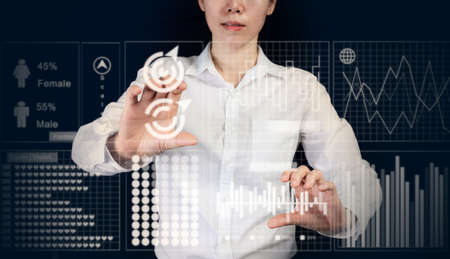 businesswoman touching virtual interface control screen reports and graphs, business planning as concept, trendy girl.