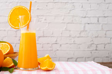 kitchen table with jug of orange juice on white brick wall texture background, front view table.