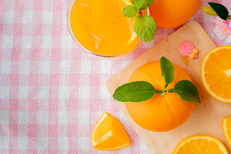 orange fruit and glass of cold orange juice on pink tablecloth, view from above table.
