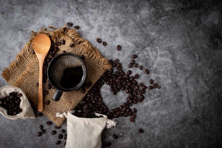 black coffee with coffee beans on cement table texture background, view from above table. 版權商用圖片