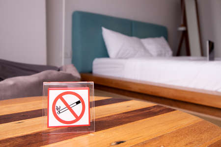 No smoking sign on wooden table in bedroom, empty room.