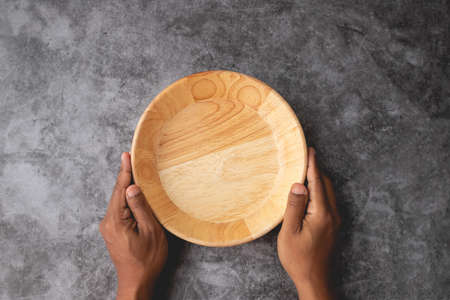 human hand hold empty wooden plate on dark cement wall texture background.