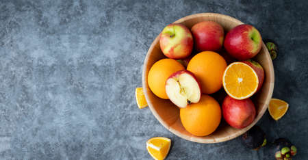 high vitamin c fruits on wooden plate, apple and orange fruits, view from above table.