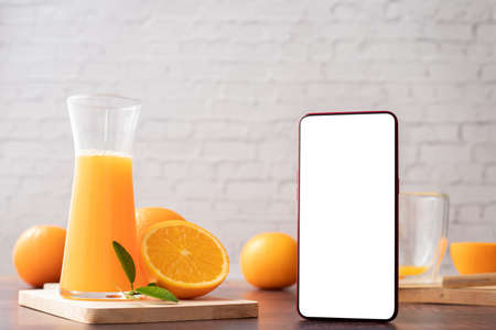 Kitchen table with Blank screen smart phone, cell phone, tablet and jug of orange juice and sliced orange. 版權商用圖片