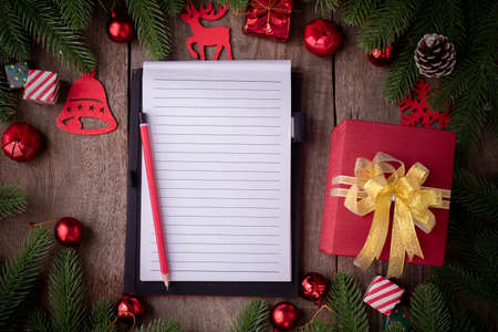 Blank screen for text notepad paper with Christmas decorations, gift boxes on wooden board, view from above.