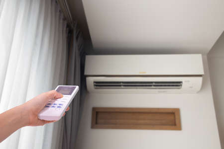 human hand pressing remote control air conditioner in living room.