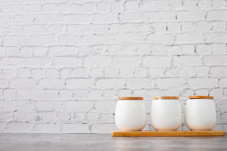 ceramic cups on white brick wall texture background, copy space.