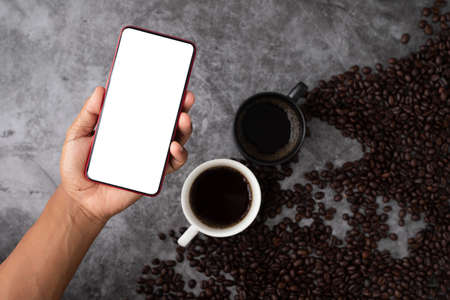 blank screen on smart phone, cell phone, tablet on black coffee cup and coffee beans.