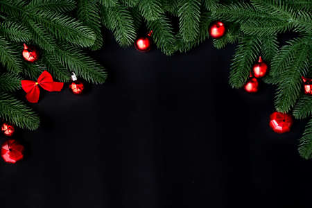 Christmas decoration frame background with fir branches and red baubles on a dark background., view from above.