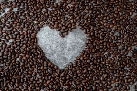 coffee beans with heart shape sign on dark wall texture background, view from above table.