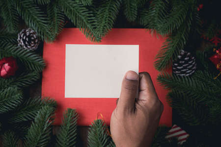 Human hand holding blank note paper on Christmas decorations background with pine leaf frame, view from above table. Stock fotó
