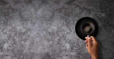 human hand black coffee cup with copy space on grunge cement wall texture background. Stock fotó