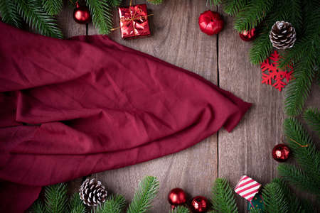 Copy space on Red fabric texture and Christmas background with decorations on wooden board, view from above.