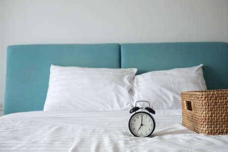 classic clock on white bed with wooden basket on bed in bedroom, front view.