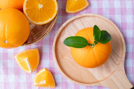 Sliced orange fruit on pink tablecloth texture background, view from above table. 版權商用圖片