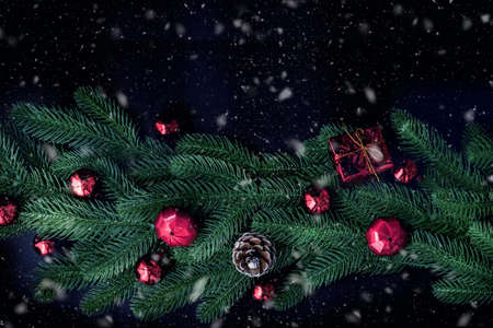 Christmas decorations with fir branches pine tree and red baubles on a dark background, view from above. 版權商用圖片