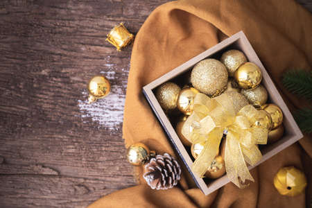 Wooden table with Christmas Decorations with Gold bauble on box