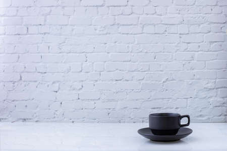 cup of tea on white brick wall texture background, view from front table.