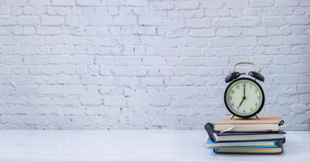 classic clock on book stack with white brick wall texture background, view from front table. 版權商用圖片