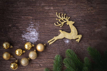 Gold Reindeer with bauble on wooden table, Christmas decorations background, view from above. 版權商用圖片