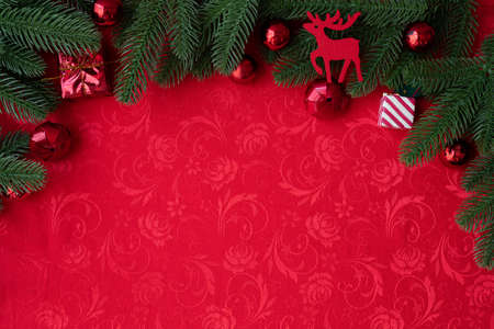 Christmas background with decorations and wide arch shaped leaf frame on red background, view from above table.