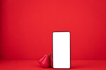 Blank screen on Mobile, cell phone, smart phone with Rose Apple Fruit on red background.