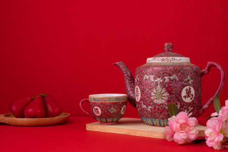 Teapot and sakura flower on red background, Chinese new year background.