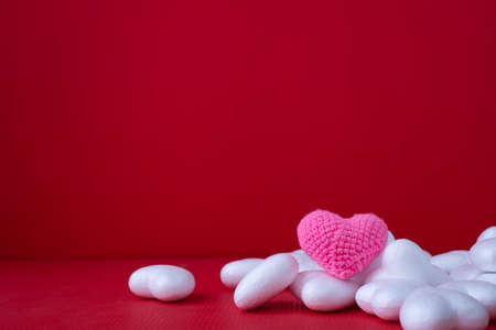 Copy space on Red Valentines background with Pink heart shape toy.
